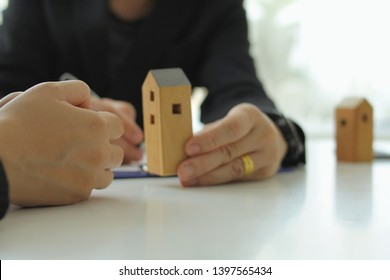 woman's hands behind the scenes have a house model placed on a white table.