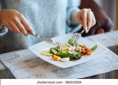 Woman's hands with Caesar salad on table in restaurant