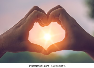 Womans hands catching sunlight sunrays while making heart shape