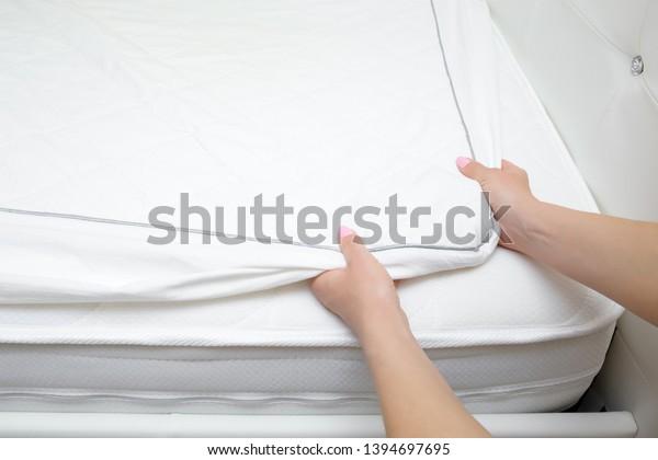 Les mains d'une femme changeant de couverture de matelas blanc. Le linge de lit change régulièrement. Gros plan. Vue du haut vers le bas.