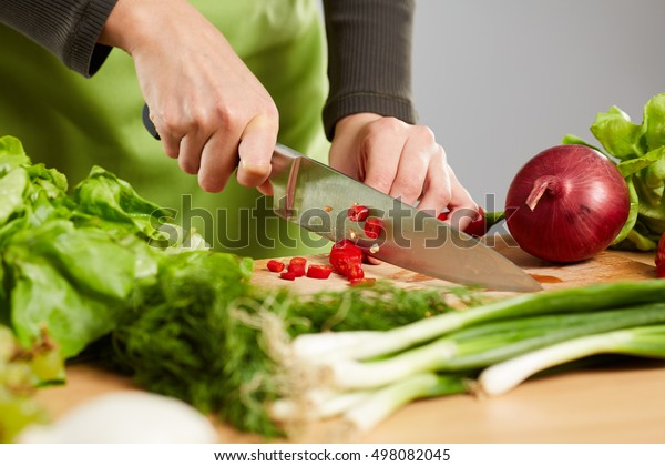 Woman's hands chopping vegetables on a wooden board