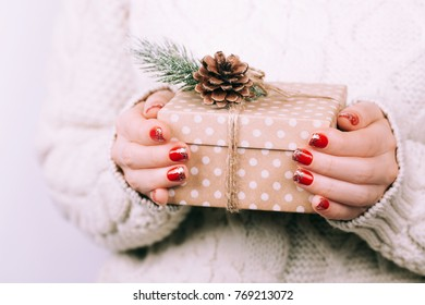 Woman's hands with christmas gift box, decorated with pine branches. Accurate red festive manicure.