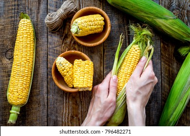 Woman's hands clean corn cob. Rustic wooden background top view