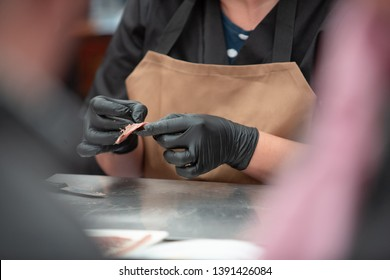 Woman's hands cleaning an anchovy. A woman working with fish making anchovy fillets.