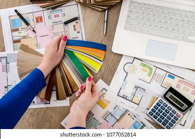 Woman's hands with color samples , house plan, laptop and calculator