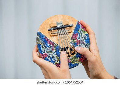 Woman's hands with colorful musical instrument Kalimba. Close view.