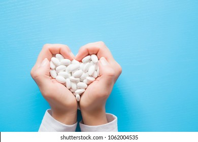 Woman's hands created a heart shape. White pills. Mock up for special offers as advertising or other ideas. Medical and healthcare concept. Copy space. Empty place for text or logo on blue background.