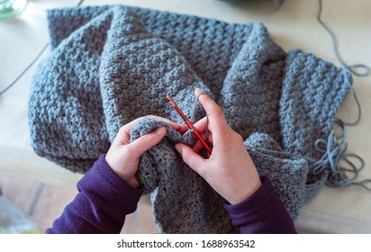 Woman's hands crochet background.  Close up Woman's hands  Crocheting blanket out of light blue yarn