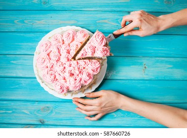 Woman's hands cut the cake with pink cream on blue wood background. Pink cake. Top view
