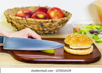 Woman`s hands cut the marinated cucumber into slices near burger