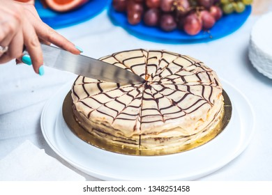 Woman's hands cut whole esterhazy torte cake with knife. Authentic recipe, hungarian and austrian dessert, view from above, close-up
