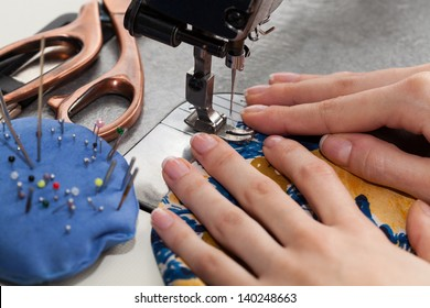 Woman's hands with dress at sewing machine