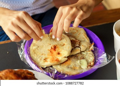 Woman's hands eating corn pupusas with cheese and beans made in El Salvador.