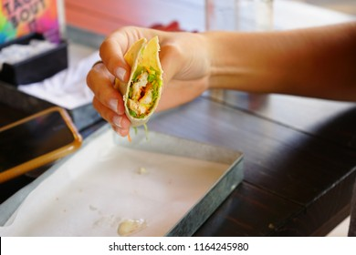 Woman's hands eating tacos in a restaurant.