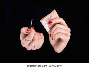 Woman's hands with euro banknotes and car keys   in a black background
