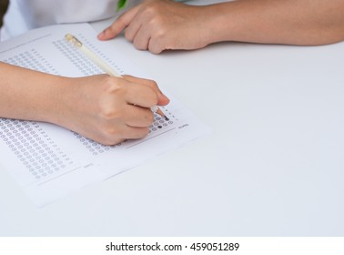woman's hands filling in standardized test form