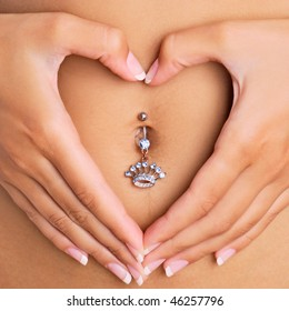 A woman's hands forming a heart symbol around navel with piercing