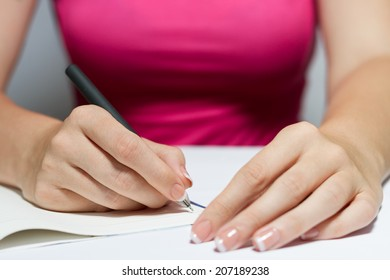 Woman's Hands With French Manicure Holding A Pen Writing A Text