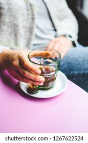 Woman's hands with a glass of coffee on a pink table