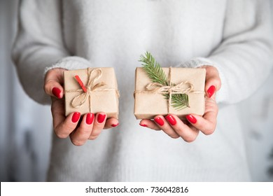 Woman's hands hold christmas or new year decorated gift box. Toned picture.