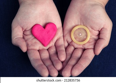 Woman's hands hold a heart shape and a condom. Concept image.