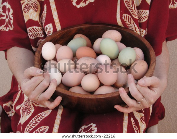 A woman's hands hold a wooden bowl full of different naturally colored eggs.
