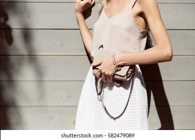 Woman's hands holding beige trendy clutch in front of the wooden wall in summer time outside in the streets. Fashion accessories. Streetstyle summer spring photo