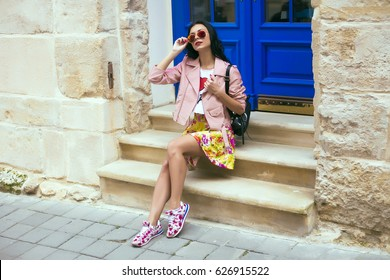 Woman's hands holding beige trendy clutch bag in front of the old city street over wall in summer time outside in the streets. Fashion accessories. Street style summer spring photo,floral sneakers