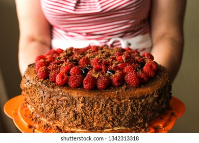 Woman's hands holding Birthday cake with fresh berries at home.