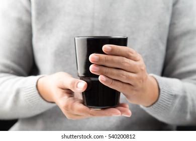 Woman's hands holding a  black ceramic mug.