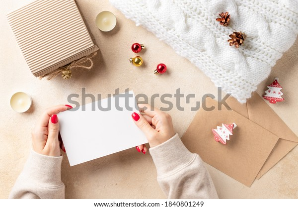 woman's hands holding blank card and xmas decorations on beige background. Flat lay for Merry Christmas or Happy New Year. Preparation for holidays. Copy space.