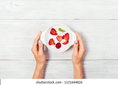 Woman's hands holding a bowl of strawberry ice cream on white wooden table, top view. Cold dessert, decorated with red berries and green leaf mint, simple flat lay composition.