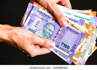 Woman's hands holding brand new indian 50, 100, 200, 500, 2000 rupees banknotes.