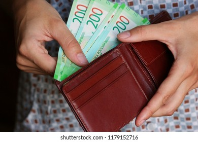 Woman's hands holding brown leather wallet with new banknotes nominal 200 rubles. Russian cash money.