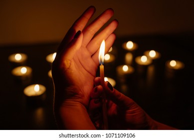 Woman's hands holding a burning candle. Abstract candles background. Many candle flames glowing on dark background. Close-up.