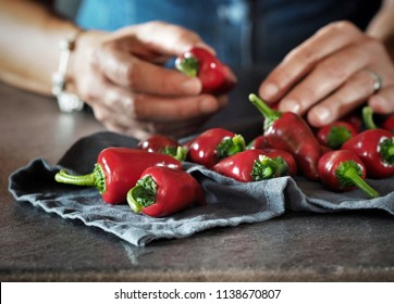 Woman's hands holding chilli peppers.