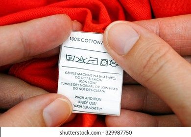 Woman's hands holding clothes label. 100 % cotton. Cleaning instructions.