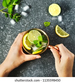 Woman's hands  holding a copper mug of lemonade with fresh mint, top view