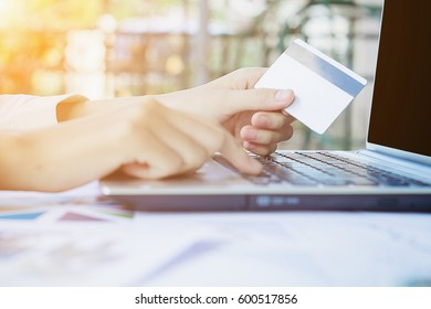 Woman's hands holding a credit card and using smart phone for online shopping.vintage tone