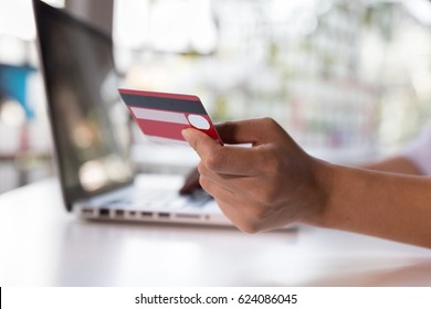 Woman's hands holding a credit card and using laptop computer for online shopping payment
