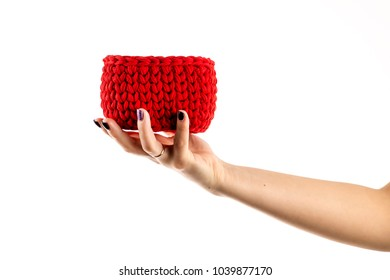 Woman's hands are holding crocheted basket red color isolated on white background.