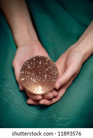 Woman's hands holding a crystal ball. Closeup, sparkly bubbles in the ball