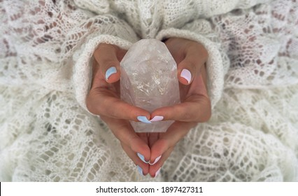 Woman's hands holding crystal. Concept of occult symbolism and spiritual practice.