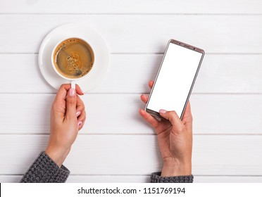 Woman's hands holding cup of coffee and using smarphone, top view