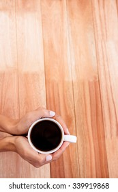 Womans hands holding cup of coffee on wooden desk