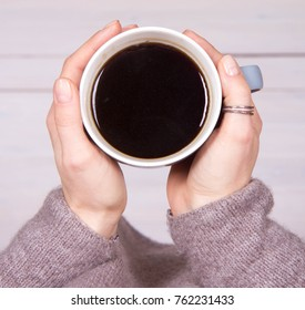 Woman's hands holding a cup of coffee over a wooden floor