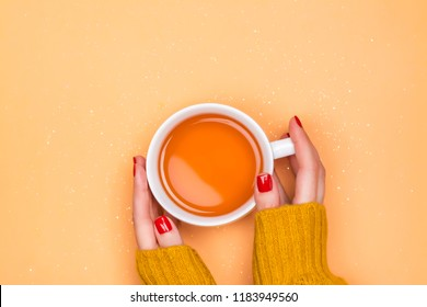 Womans hands holding cup of hot tea on autumn background. Cozy autumn mood. Flat lay style, copy space