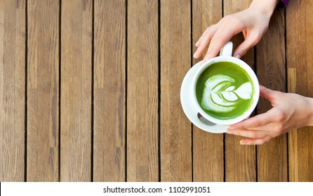 Woman's hands holding cup matcha green tea latte on wooden background. Top view, flat lay, copyspace for text