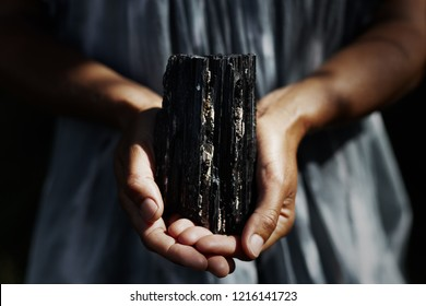 Woman's hands holding dark, powerful black tourmaline crystal