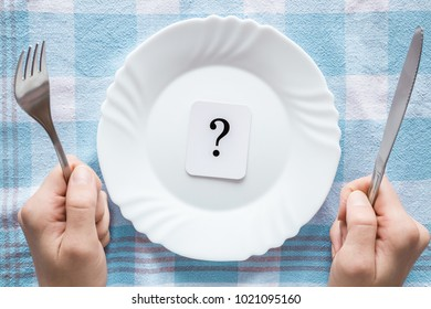 Woman's hands holding a fork and knife. Question mark in the clean, empty, white plate on the tablecloth. Starving people. Meal waiting concept. Top view.